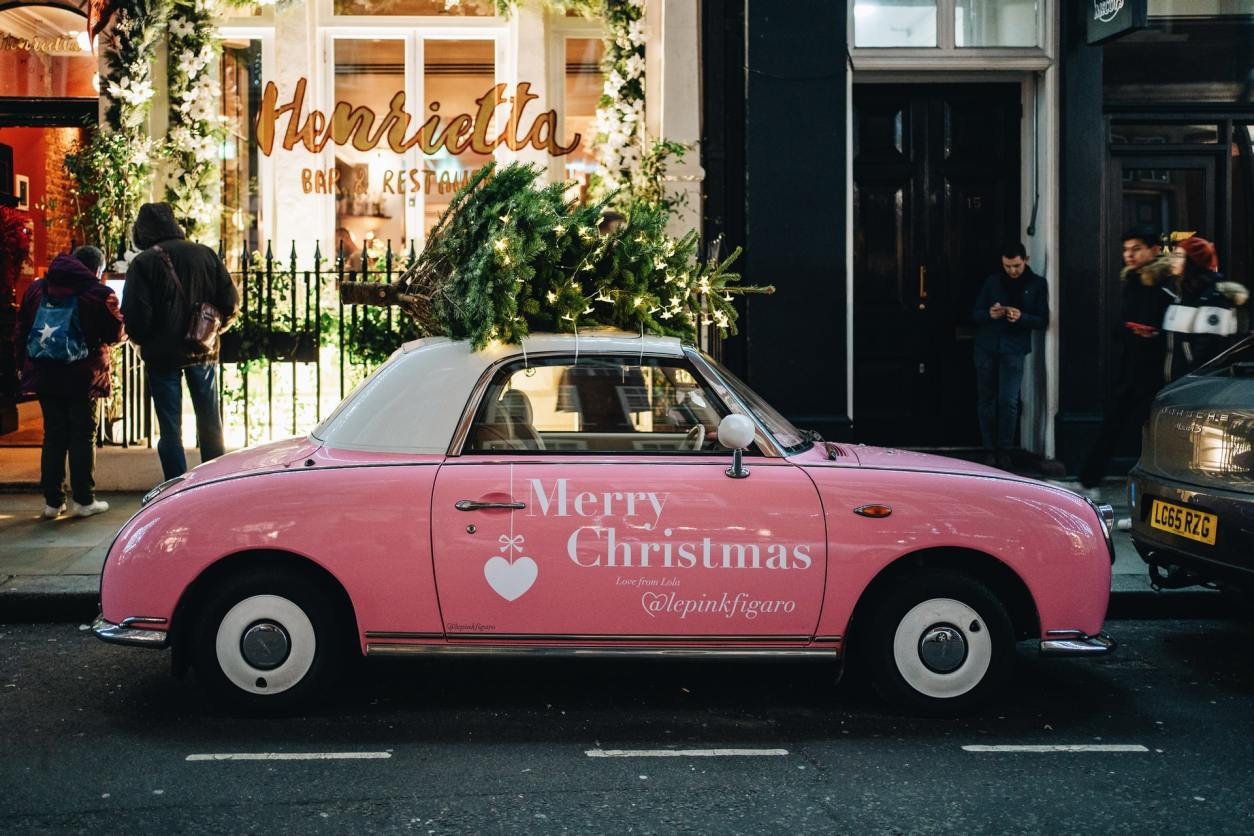 pink-car-parked-up-against-pavement-with-christmas-tree-on-top-of-it-in-covent-garden
