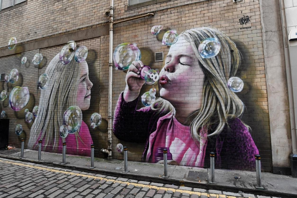 street-art-grafitti-of-a-girl-blowing-bubbles-on-glasgows-mural-trail