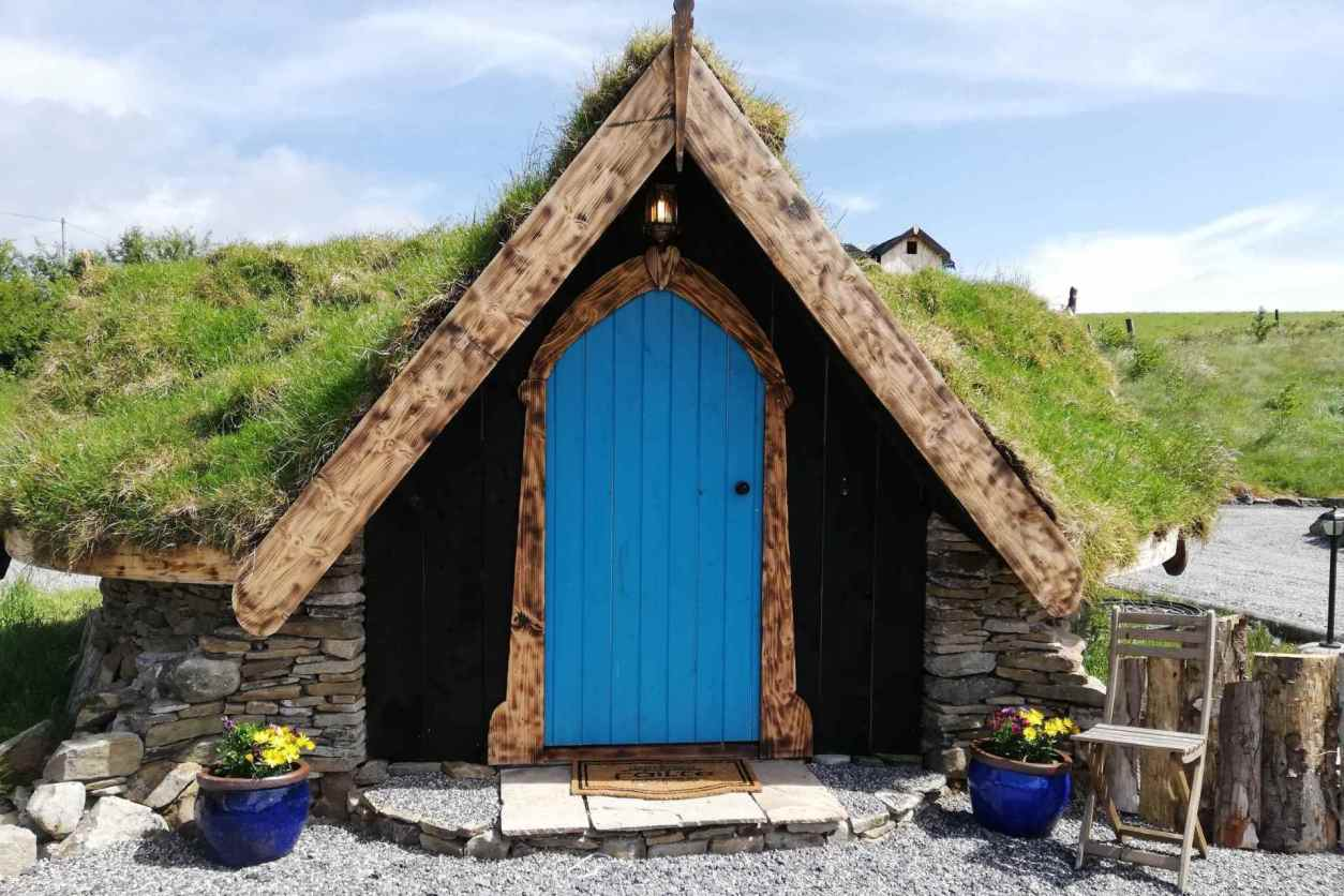 an-claddagh-fairy hut-under-grassy-hill-with-blue-door