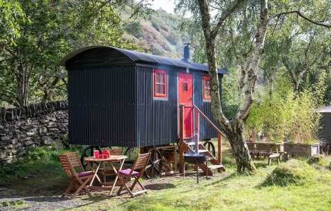 blue-and-red-shepherds-hut-in-field-with-mountains-in-background-graig-wen-glamping-snowdonia