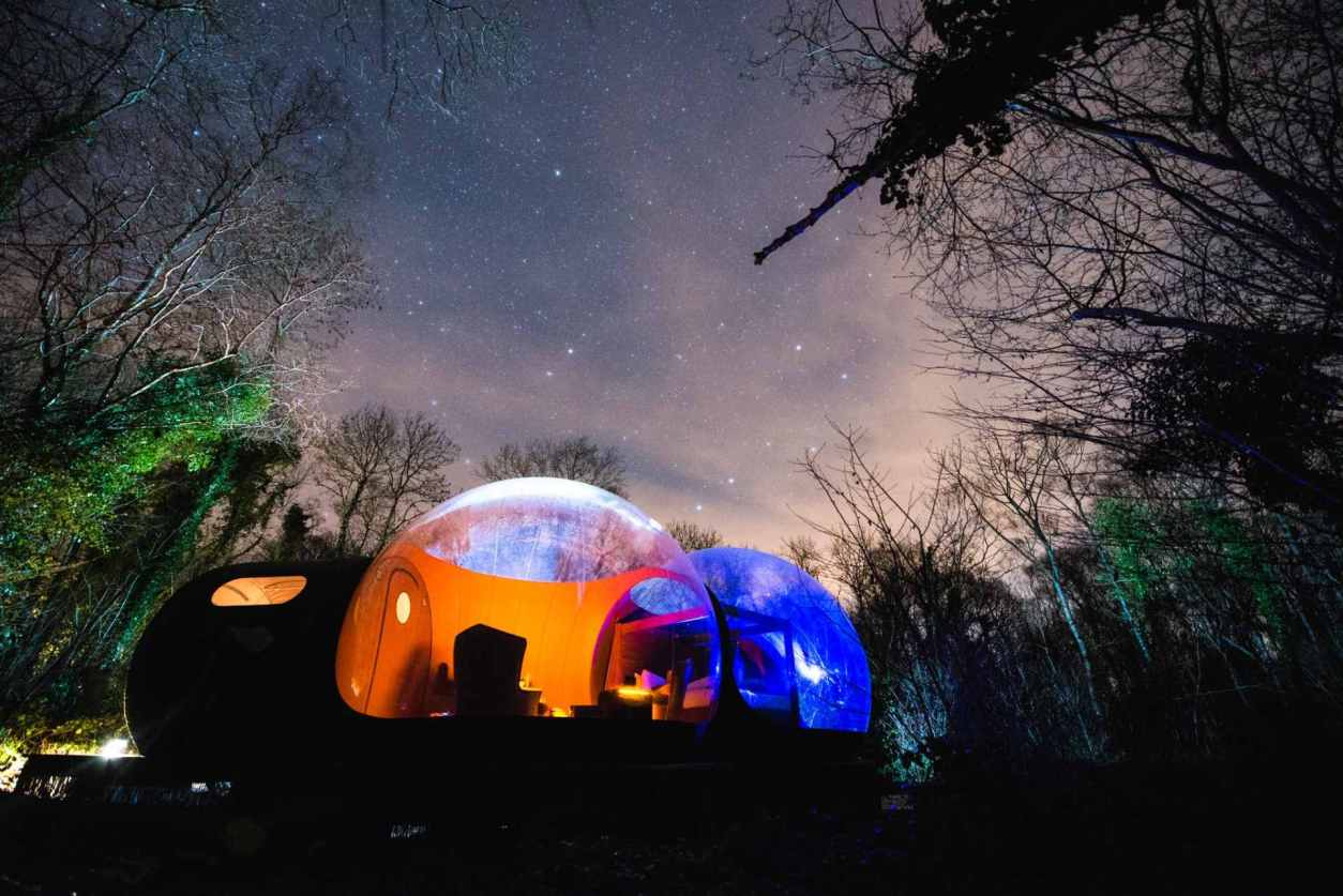 bubble-dome-lit-up-at-night-in-forest-under-stars-at-finn-lough-glamping-northern-ireland