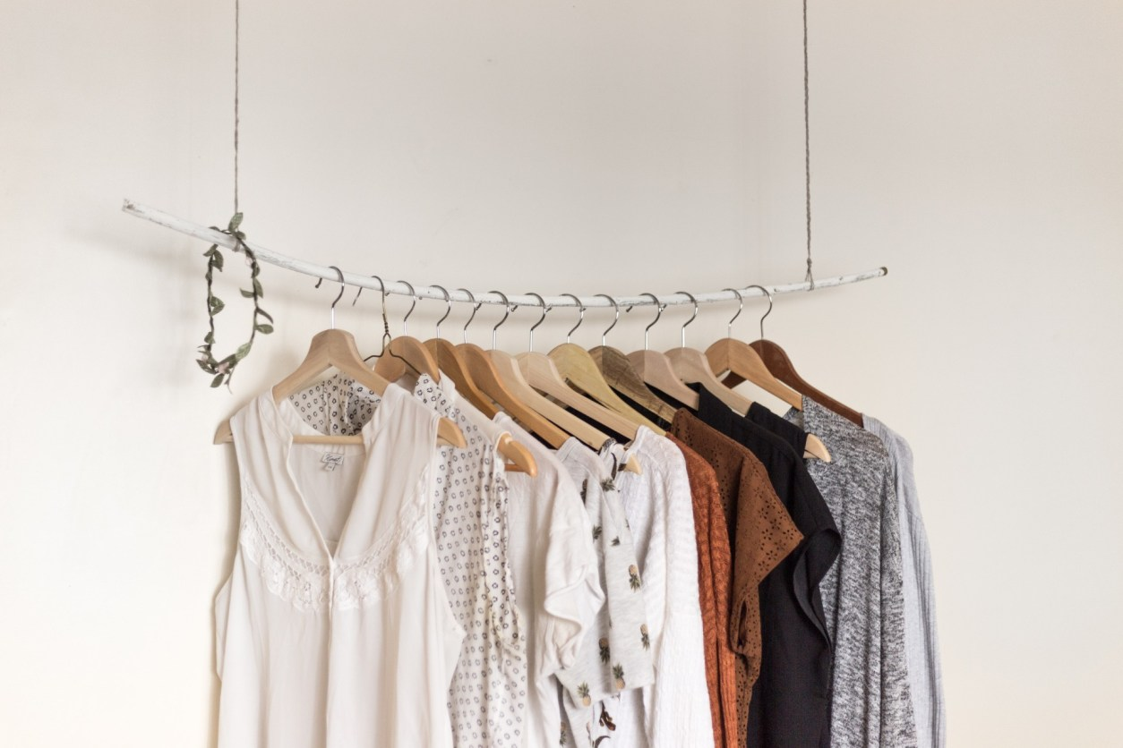 clothes-hanging-from-hanging-rail-from-ceiling-in-white-minimalist-room-travel-capsule-wardrobe