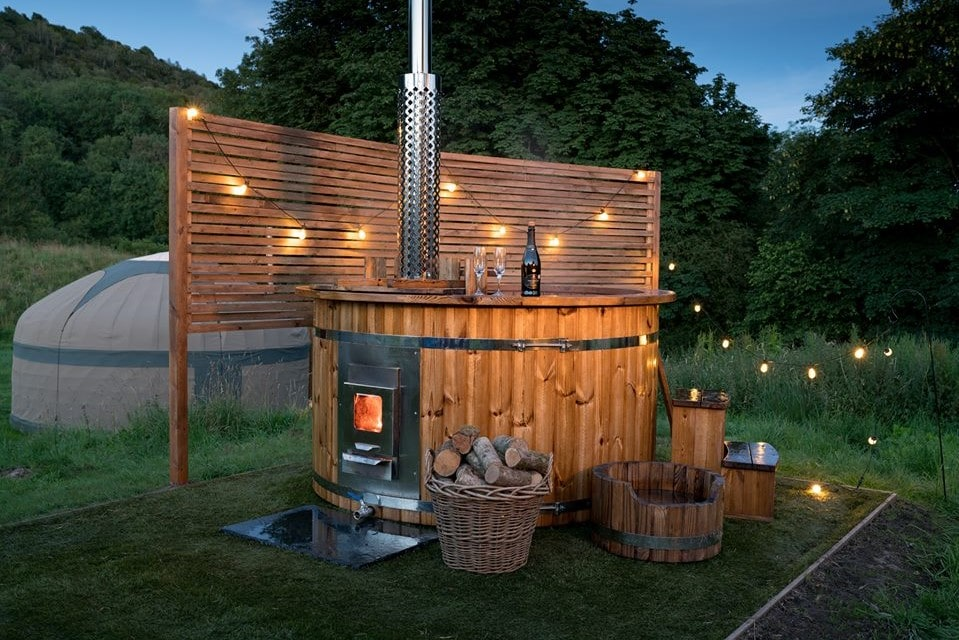 long-valley-yurts-outdoors-hot-tub-on-grass-at-sunset-in-dark-lit-up-by-fairy-lights