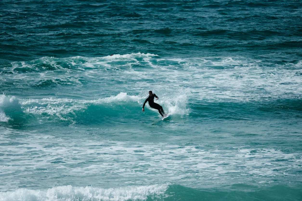 man-in-black-wetsuit-surfing-on-turquoise-sea