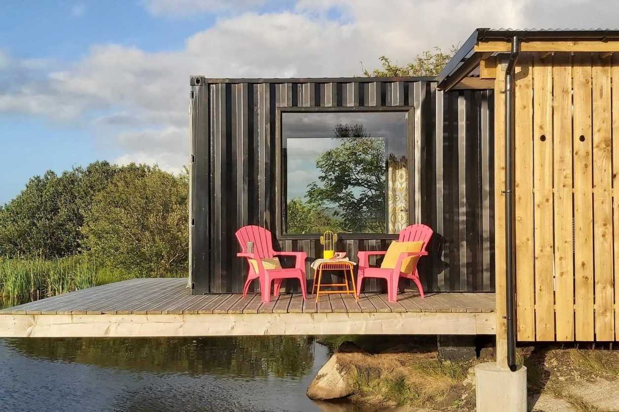 pink-chairs-on-decking-over-lake-at-frank-the-shipping-container-glamping-donegal