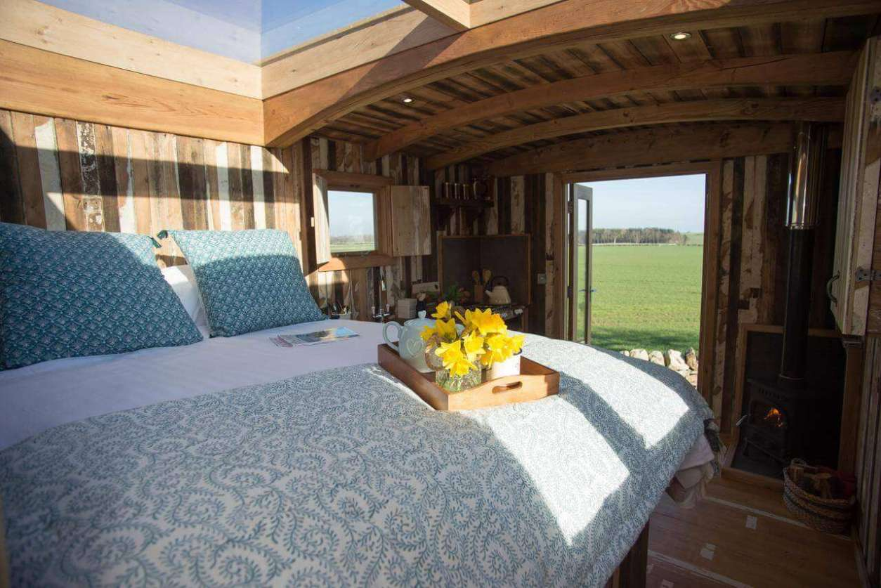 bed-with-sky-light-inside-beadnell-shepherds-retreats-hut-glamping-northumberland