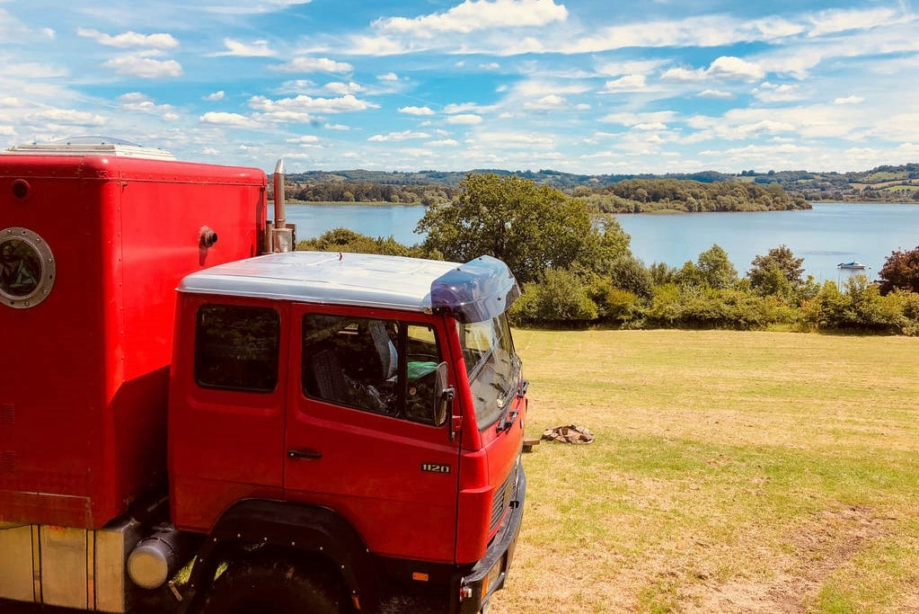 big-red-truck-in-a-field-on-herons-green-farm-with-lake-views