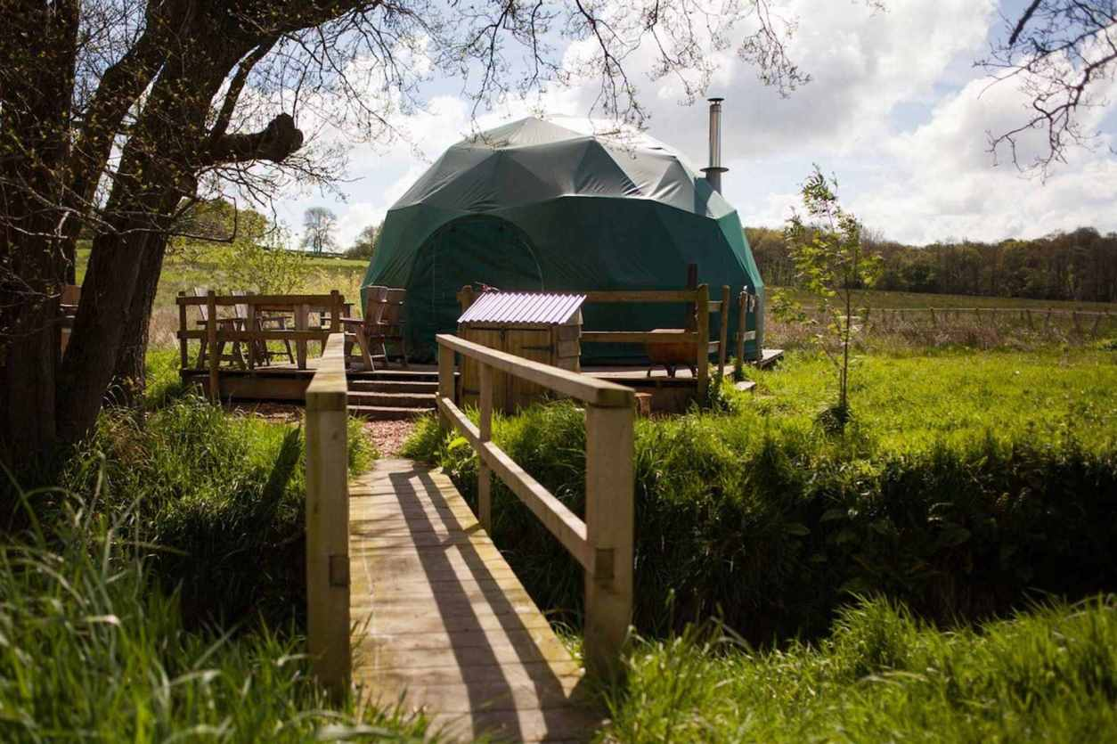 bridge-leading-to-green-glamping-geodome-in-field-at-cosy-under-canvas-glamping-herefordshire
