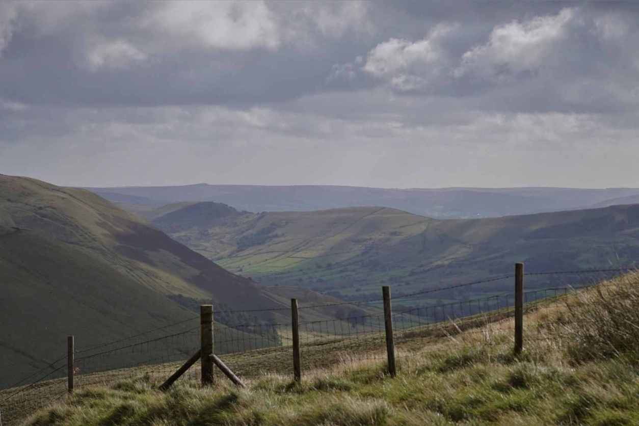 brown-wooden-fence-on-green-grass-field-overlooking-mountains-on-cloudy-day-kinder-scout