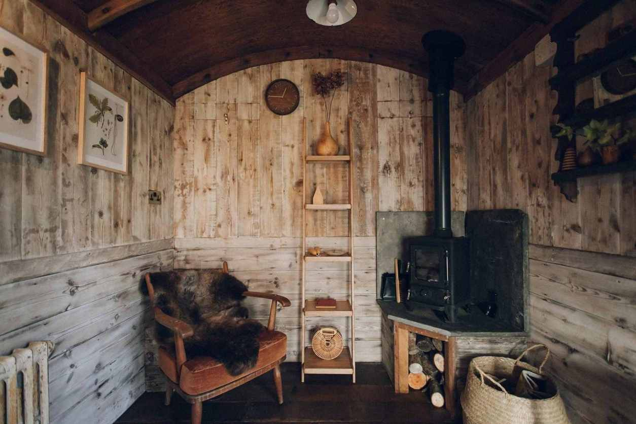 cosy-seat-and-woodburner-living-area-inside-restored-wooden-train-carriage-glamping-at-settle