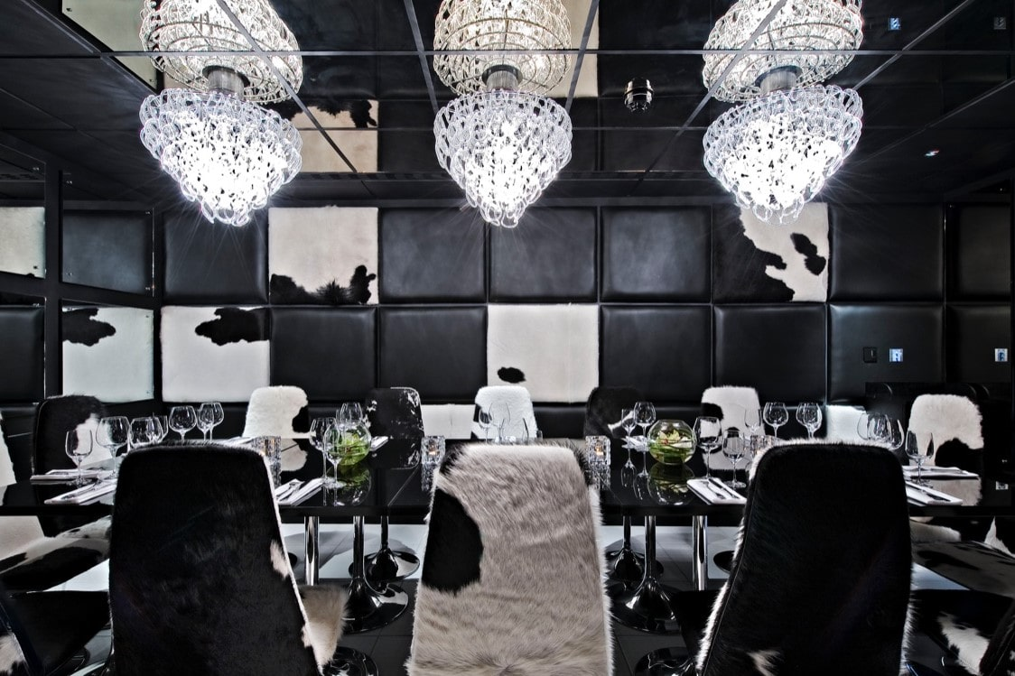 dark-cow-print-room-with-a-dining-table-chairs-and-chandeliers-at-gaucho-restaurant