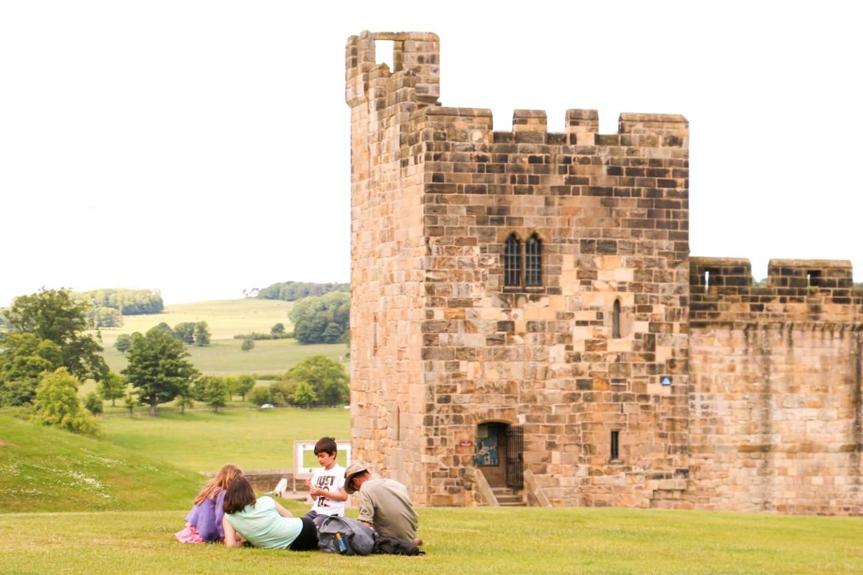 family-of-four-having-a-picnic-on-grass-by-alnwick-castle