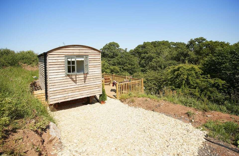 hawthorn-retreat-shepherds-hut-with-porch-terrace-overlooking-trees-on-sunny-day-airbnbs-lake-district