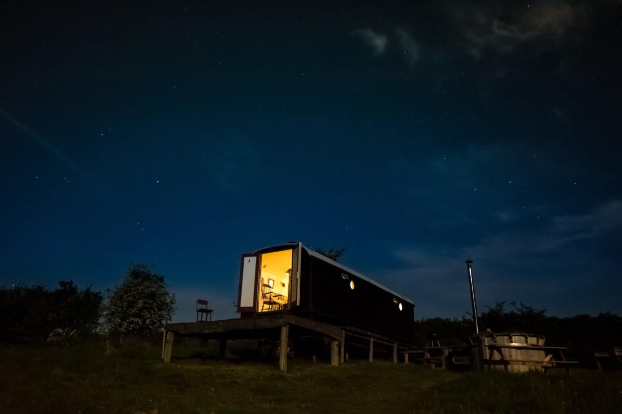 herefordshire-hideaways-stargazers-wagon-with-hot-tub-lit-up-at-night-under-a-starry-night-sky-glamping-herefordshire