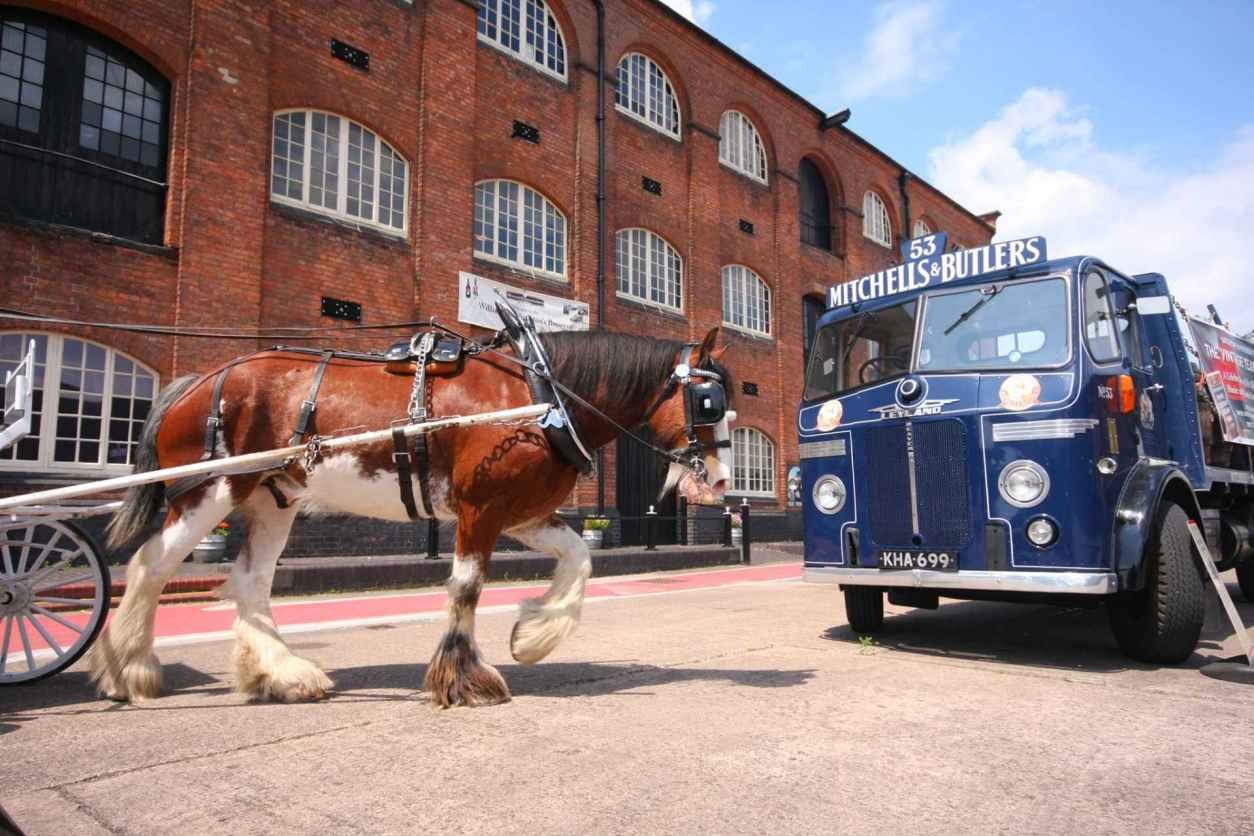 horse-pulling-cart-and-blue-truck-by-brick-building-at-national-brewery-centre-burton-upon-trent
