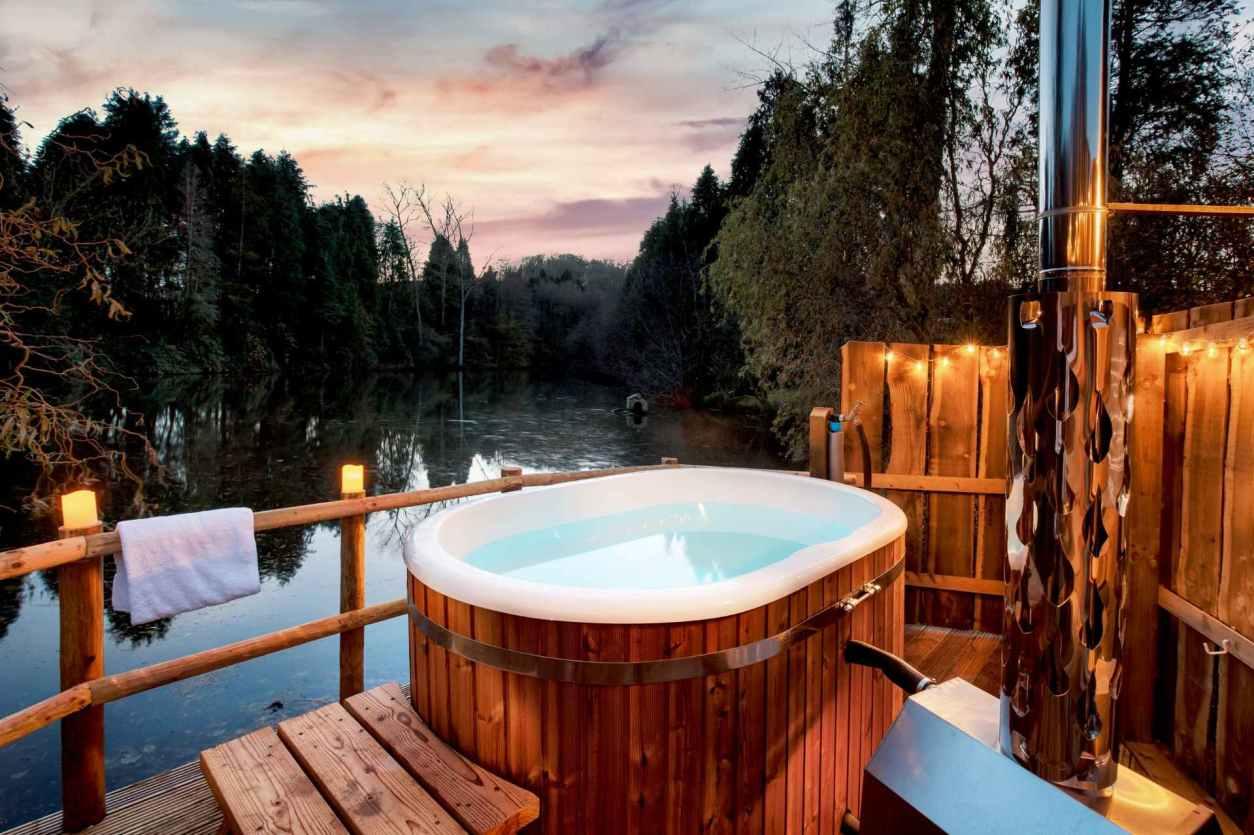 hot-tub-overlooking-lake-at-sunset-at-the-shepherds-hut-retreat-glamping-somerset