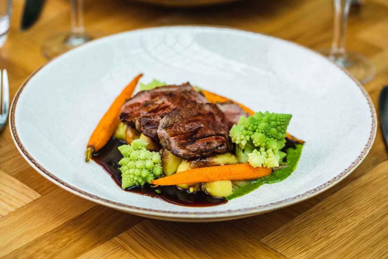 lamb-vegetables-and-gravy-in-white-bowl-on-table-at-aria-restaurant-the-hyatt