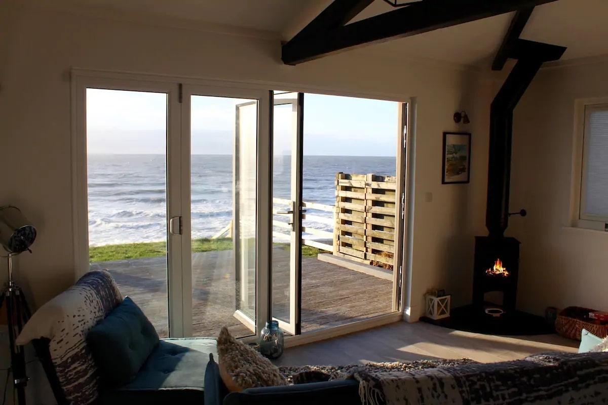 living-area-with-woodburner-overlooking-sea-brocklebank-beachfront-chalet