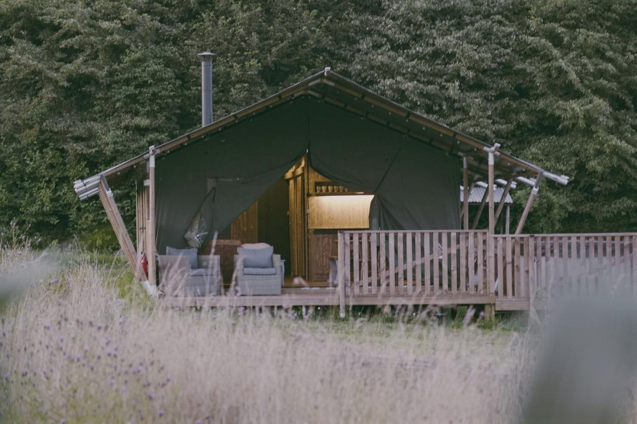 natures-nest-safari-tent-in-grassy-field-with-outdoor-seating-area