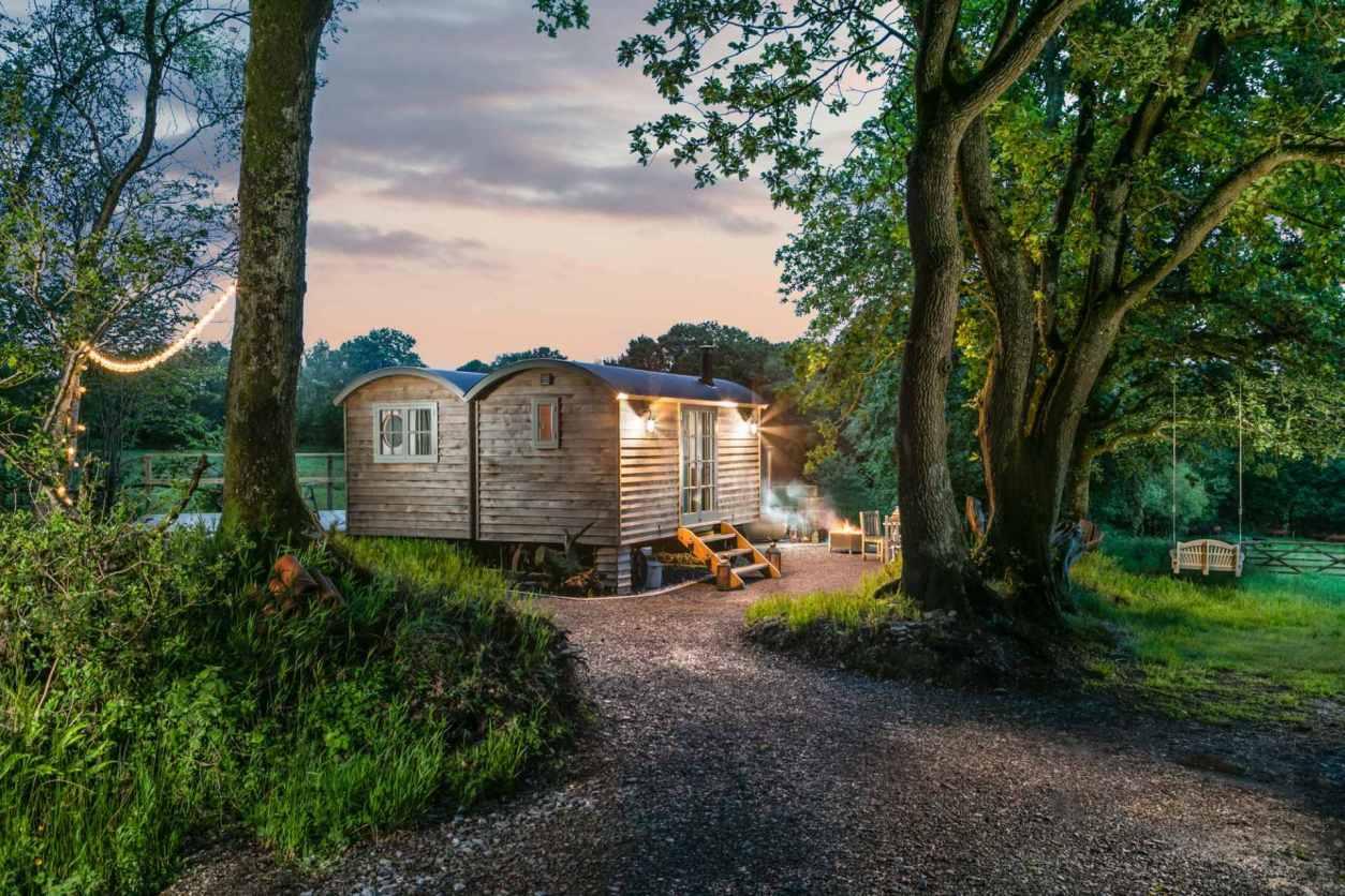 path-leading-towards-shepherd-hut-lit-up-in-evening-at-dimpsey-glamping-somerset-glamping