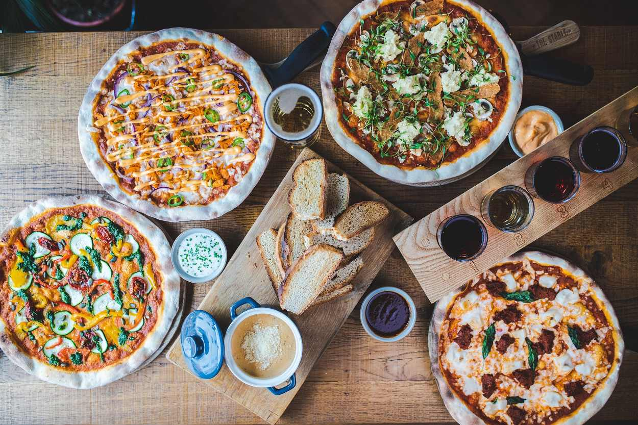 pizzas-bread-and-drinks-on-table-of-the-stable