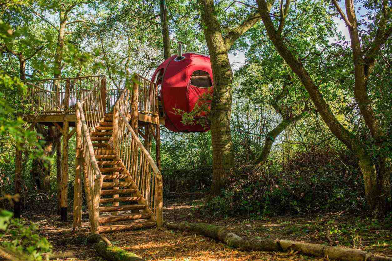 red-spherical-goji-tree-tent-suspended-in-air-at-brook-house-woods-glamping-herefordshire