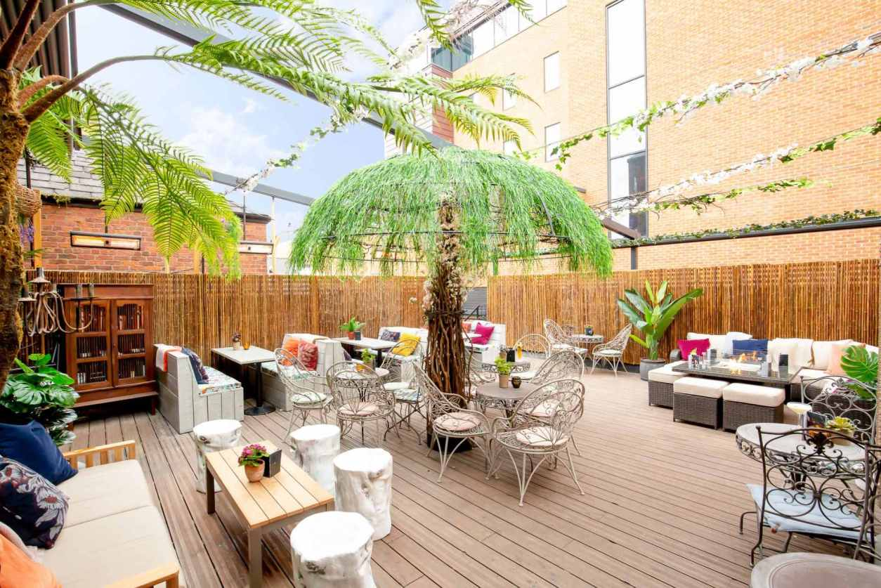 roof-terrace-with-tables-and-fake-palm-trees-at-red-door-bar-date-ideas-liverpool