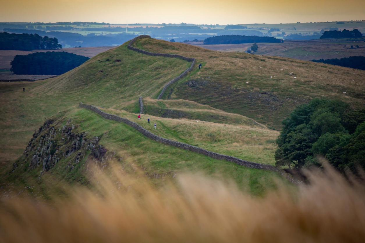 rubble-wall-hadrians-wall-winding-through-countryside-hills-at-sunset-best-places-to-visit-in-northumberland