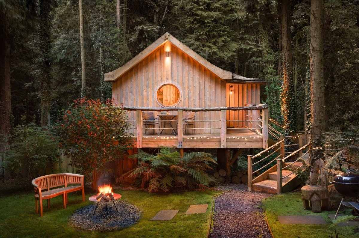 the-birdhouse-treehouse-at-the-yurt-retreat-lit-up-in-the-evening-in-woodland-glamping-somerset