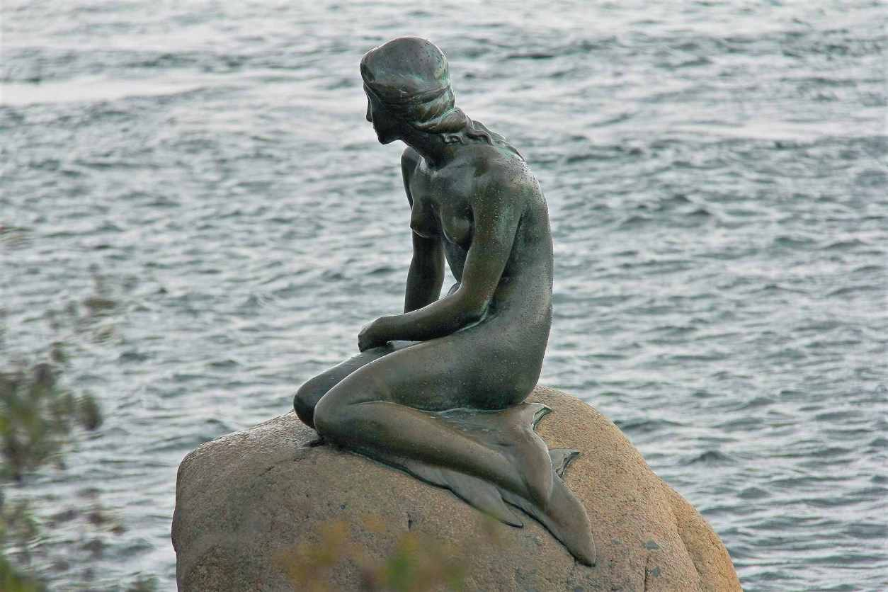 the-little-mermaid-statue-sat-on-rock-by-water