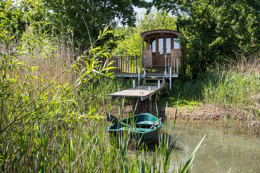 the-nancy-blackett-shepherds-hut-with-boat-on-lake-at-highgates-farm