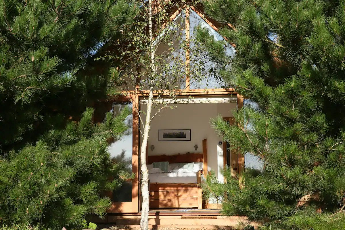 triangular-cabin-in-woodland-with-open-doors-leading-to-double-bed