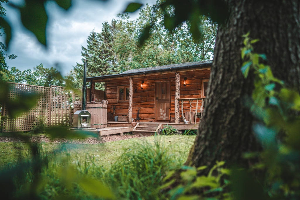 view-of-saddlers-cabin-from-behind-tree-at-woodland-chase-glamping-northumberland