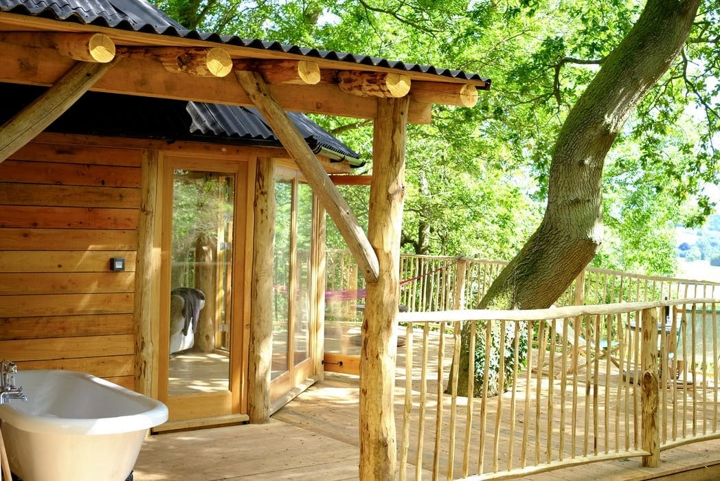 white-bathtub-on-decking-of-humboldt-treehouse-at-brook-house-woods-overlooking-fields-glamping-herefordshire