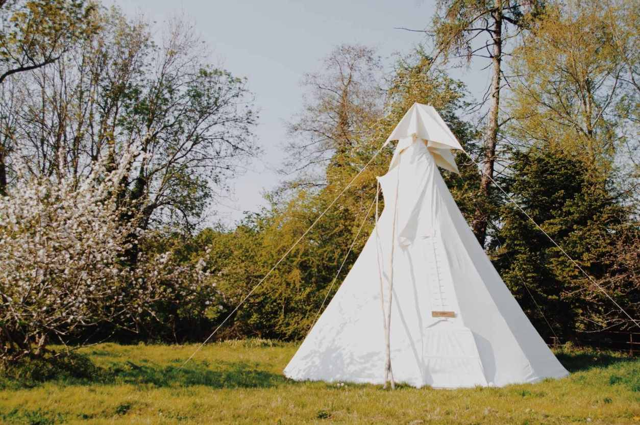 white-bell-tent-in-field-in-spring-at-white-house-glamping