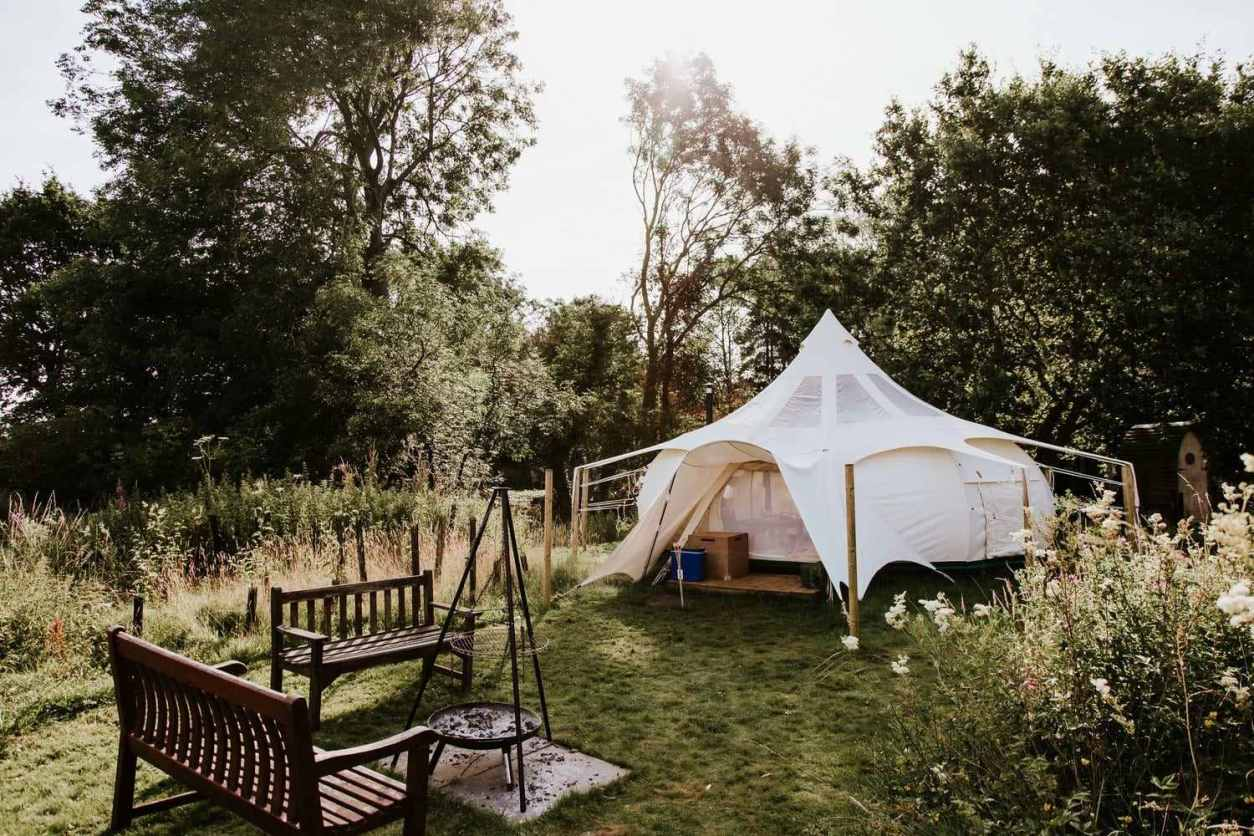 white-moat-island-stargazer-bell-tent-in-field-with-two-benches-and-firepit-glamping-norfolk