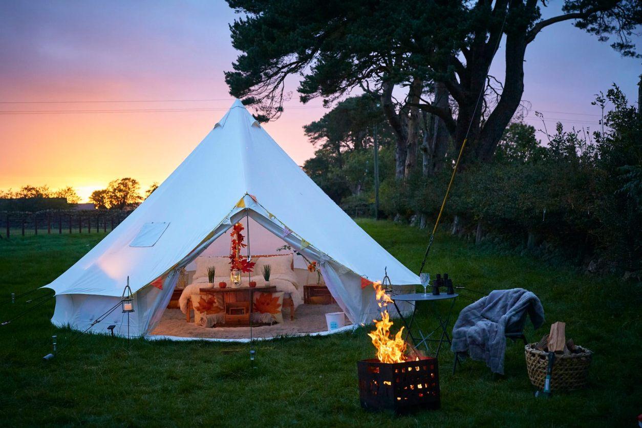 white-tipi-and-campfire-at-sunset-at-dark-sky-glamping