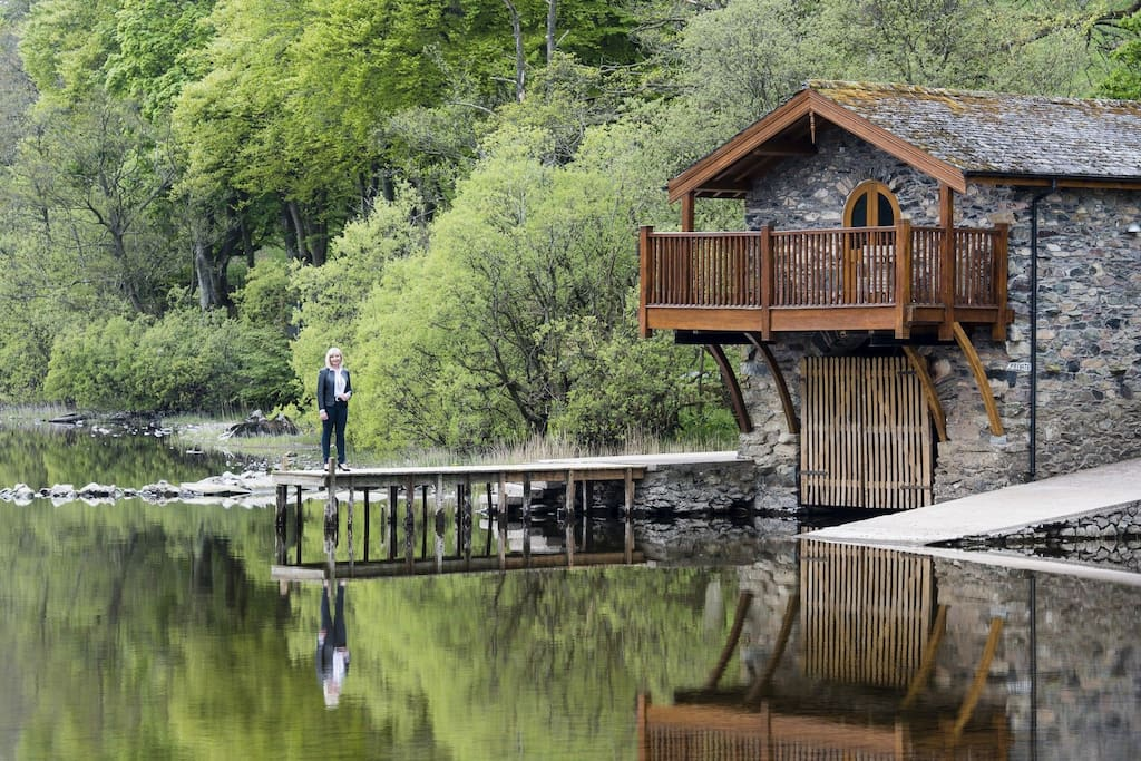 woman-standing-on-decking-of-ullswater-duke-of-portland-boathouse-airbnbs-lake-district