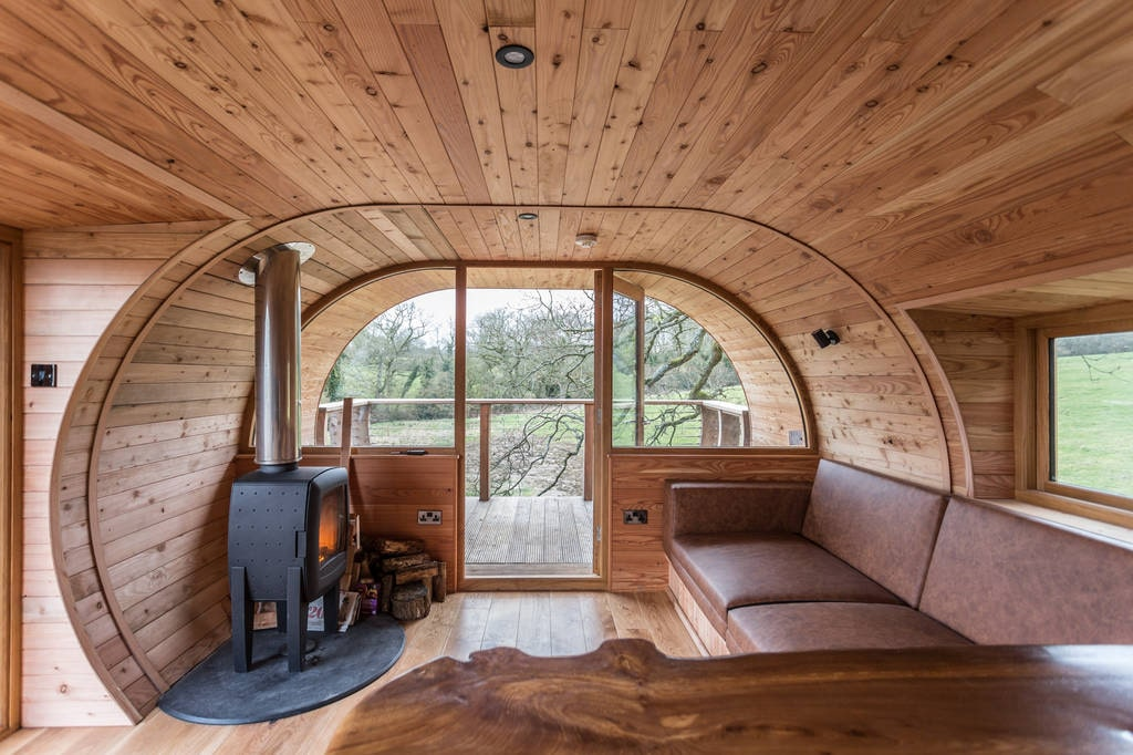 woodburner-and-sofa-in-living-area-of-cheriton-treehouse-somerset-glamping