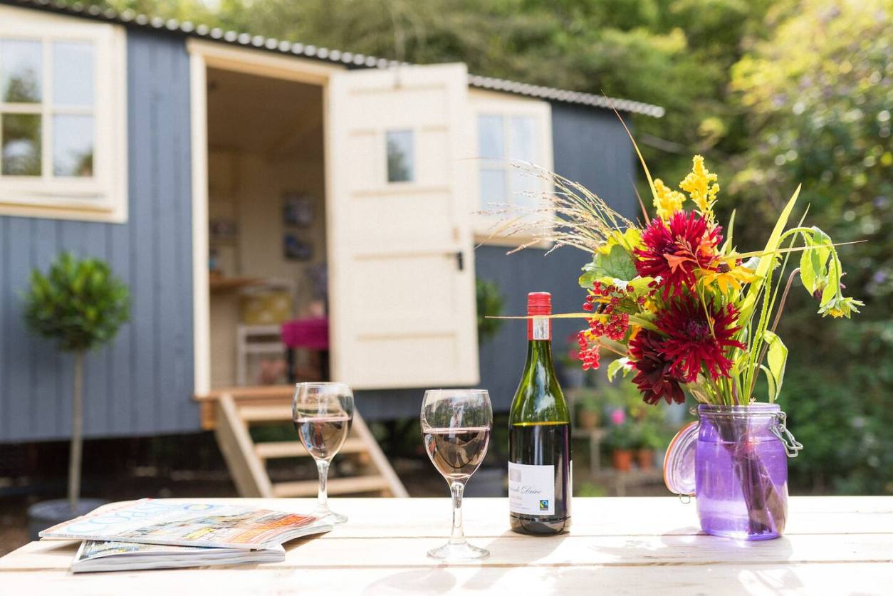 wooden-table-with-red-wine-and-flowers-in-front-of-hut-next-the-sea-shepherds-hut