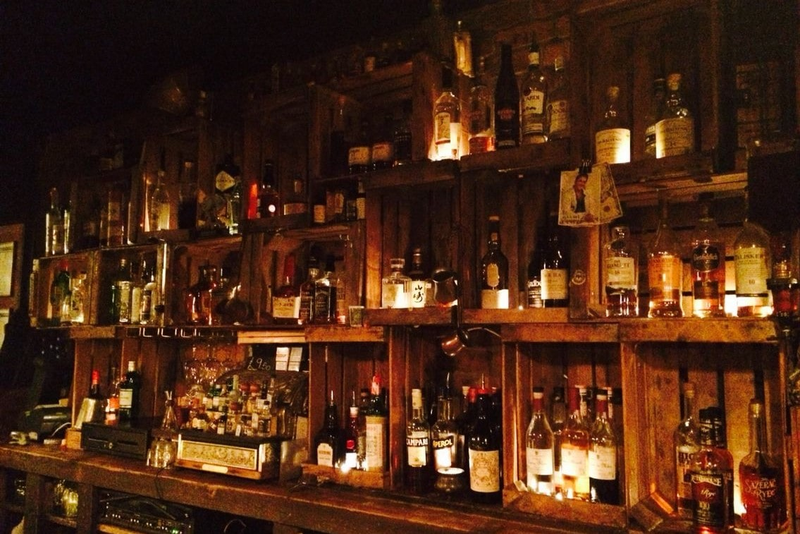 alcohol-behind-wooden-bar-at-berry-and-rye