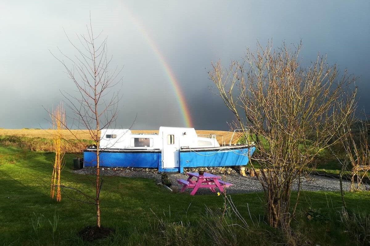 blue-and-white-land-boat-in-field-with-rainbow-in-sky