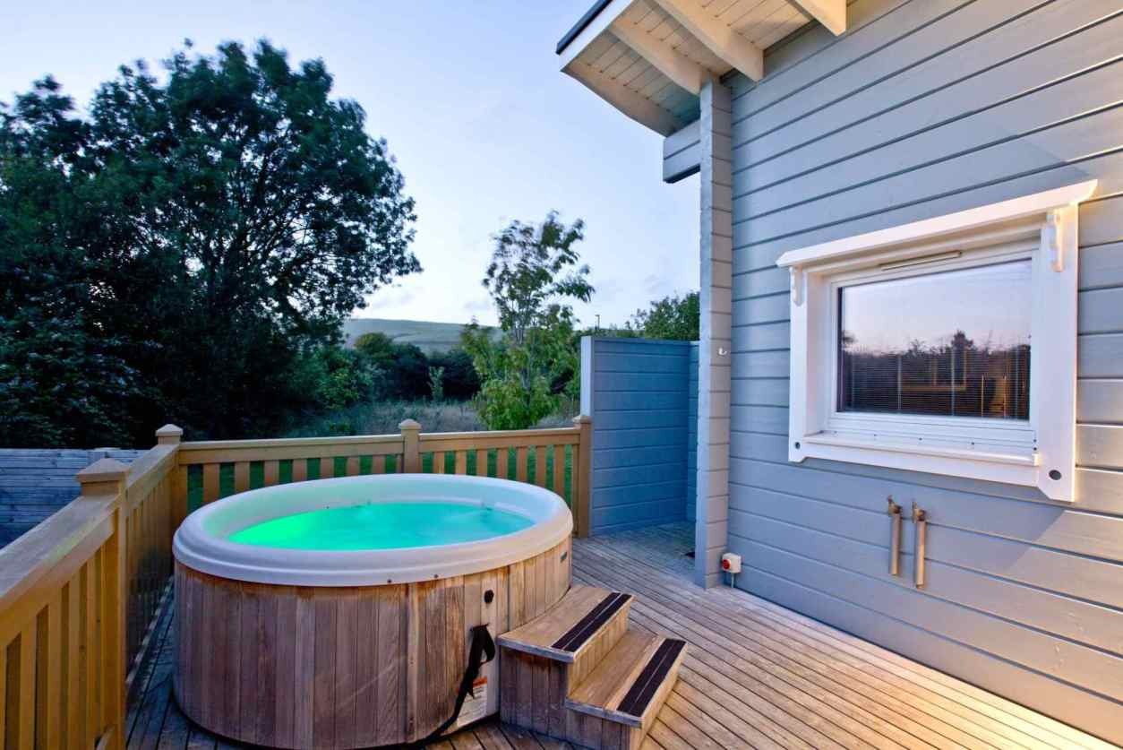 hot-tub-on-decking-of-lodge-at-great-field-lodges-at-sunset-lodges-with-hot-tubs-devon