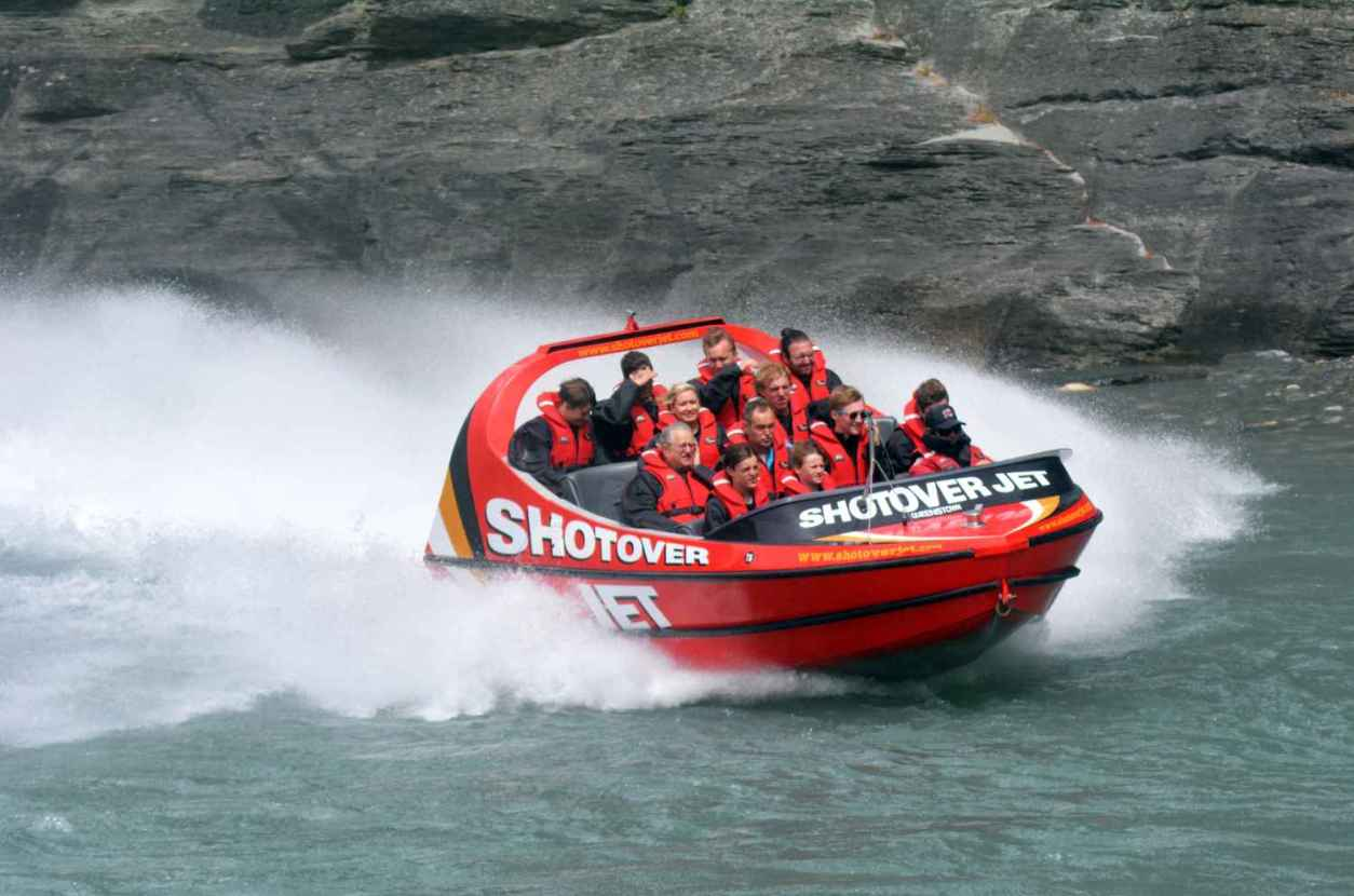 people-on-red-shotover-jet-boat-going-down-river