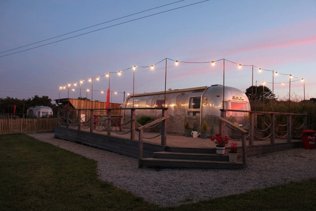 poppy-airstream-lit-up-on-decking-at-sunset