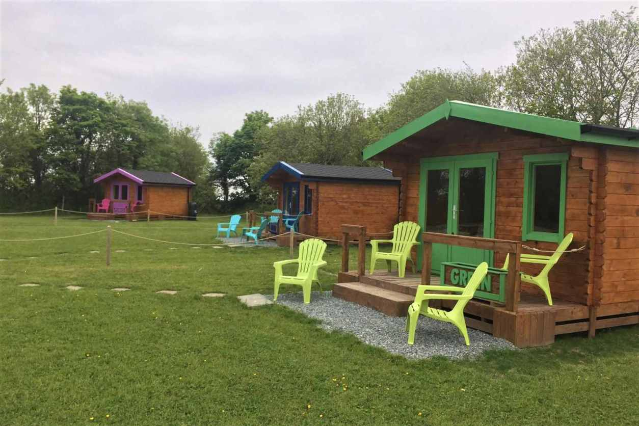 three-colourful-IOAC-glamping-cabins-in-field