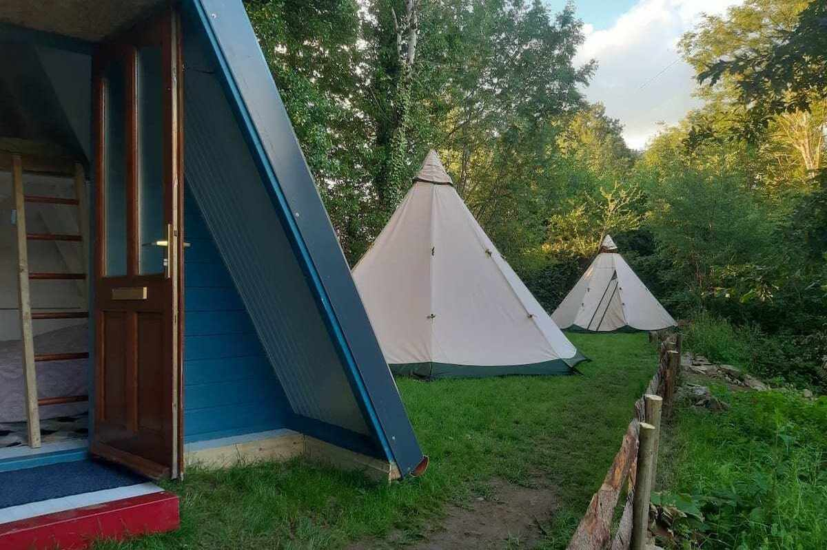 two-white-tipis-by-a-frame-cabin-at-wilton-mills-teepees-glamping-wexford
