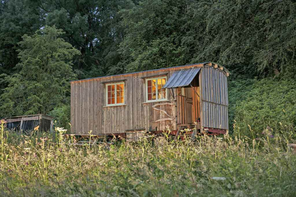 grey-gwennol-cabin-in-front-of-trees-in-field-glamping-south-wales