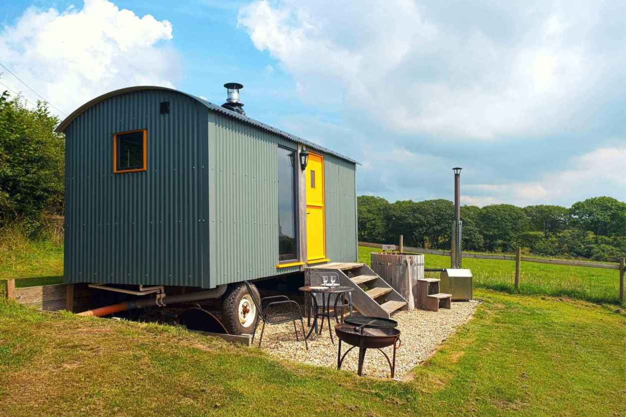 mint-big-cwtch-shepherds-hut-with-yellow-door-in-field-glamping-south-wales