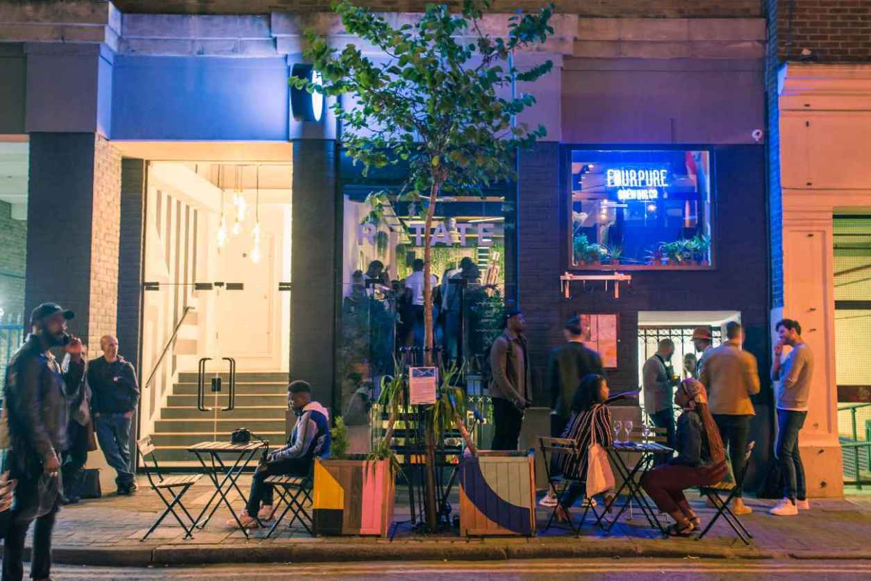 people-eating-outside-of-rotate-bar-at-night
